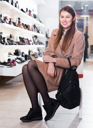 Cheerful woman is choosing modern sneackers in shoes store