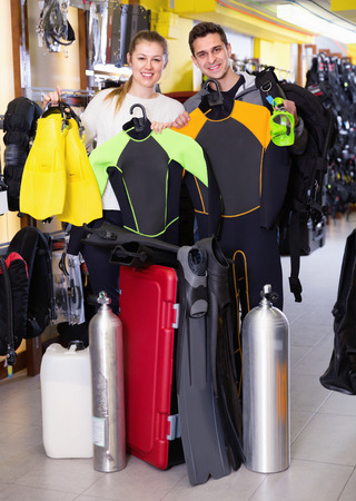 Glad cheerful smiling man and woman are standing with modern diving equipment in the store.