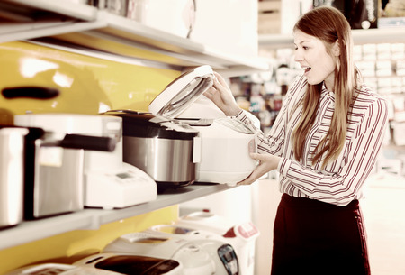 Young attractive female housewife choosing multicooker in household appliances store