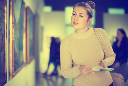 Beautiful woman visitor holding guide book standing near  pictures in museum of arts