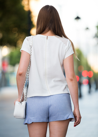 Back view of stylish young woman strolling through modern city streets