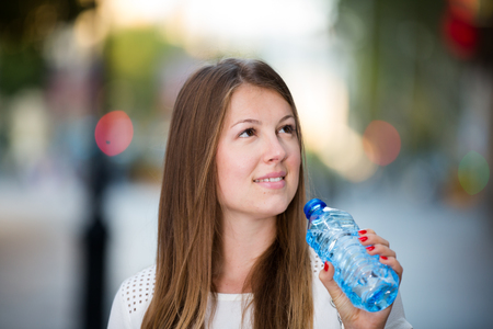 Young woman quenching thirst with water while walking through summer city