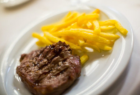striploin steak with potato chips on a white plate