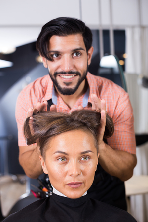 positive man hairdresser making hairstyle for woman in salon  Stock Photo