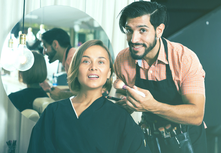 Cheerful male makeup artist in salon applying cosmetics for woman Stock Photo