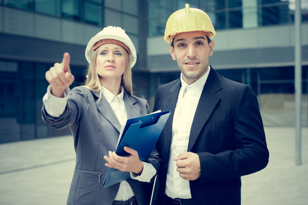 Smiling engineer and woman designer are estimating results of their project on the outside. Stock Photo