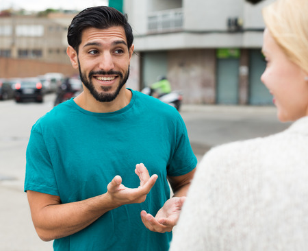 Female is talking with latino male in city.
