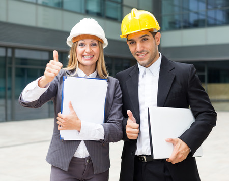Smiling engineer and woman designer are pleased with realisation their project on the outside. Stock Photo