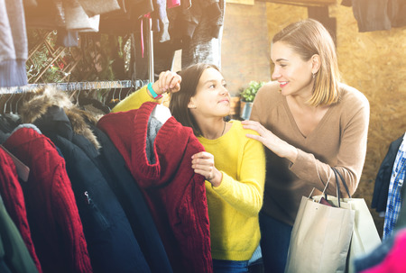 Cheerful young mother and daughter deciding on warm sweater in children's cloths shop