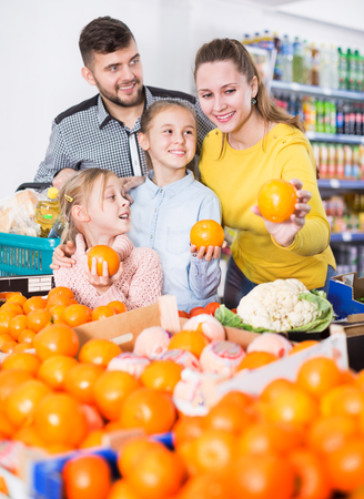 Young family of four shopping together in a greengrocery store choosing the oranges