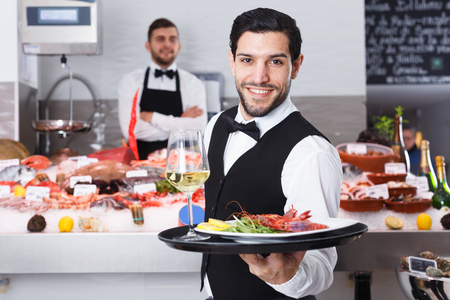 Portrait of smiling waiter with serving tray offering dishes in fish restaurant