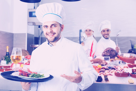 Portrait of professional  cheerful positive smiling chef with serving tray offering seafood in fish restaurant
