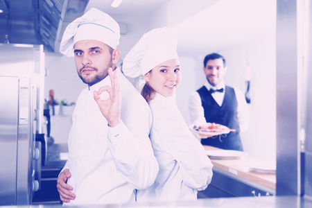 Portrait of team of professional restaurant cooks in kitchen on background waiter
