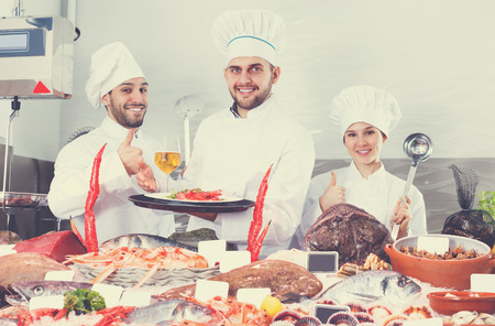 Smiling group of professional chefs of fish cafe inviting to degustation of dishes of seafood   Stock Photo