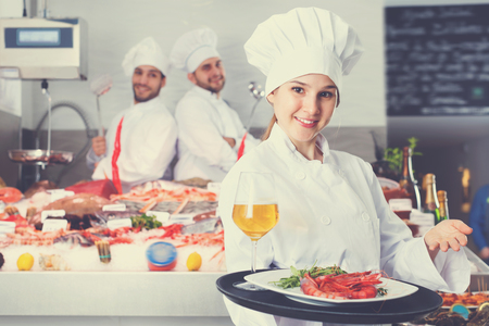 Attractive glad cheerful female chef with serving tray, offering dishes in fish restaurant