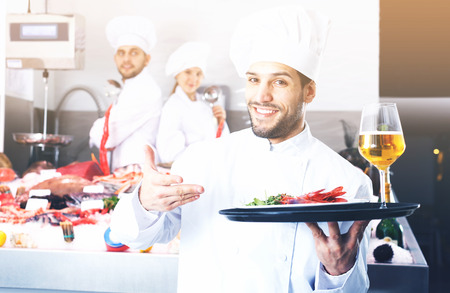 Portrait of confident smiling chef standing with serving tray in seafood restaurant