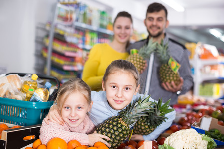 Adult parents with two little girls with pineapples in supermarket Stock Photo