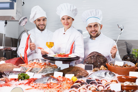 Positive group of professional chefs of fish restaurant inviting to degustation of dishes of seafood