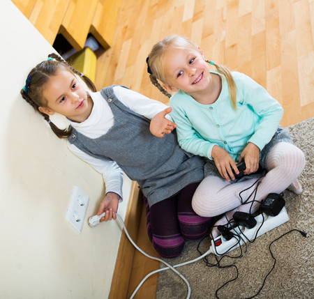 Two little girls playing with electricity and wall outlers  Stock Photo
