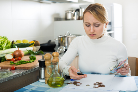 Depressed broke blonde posing in kitchen with coins and bills