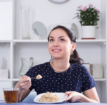 Young smiling girl sitting at table and eating cereal for breakfast  Stock Photo