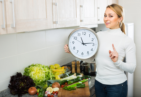 Smiling young housewife at kitchen cooking vegetables and checking time on the clock