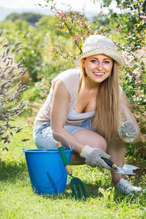 merry young woman working in garden among green plants and flowers on sunny day Stock Photo