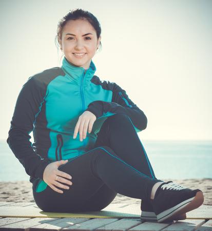 Smiling girl preparing for regular training on beach