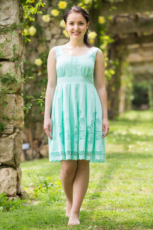 portrait of young positive woman in  dress  near roses in a garden Stock Photo