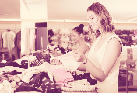 Young happy female friends shopping new basics pants in store  Reklamní fotografie