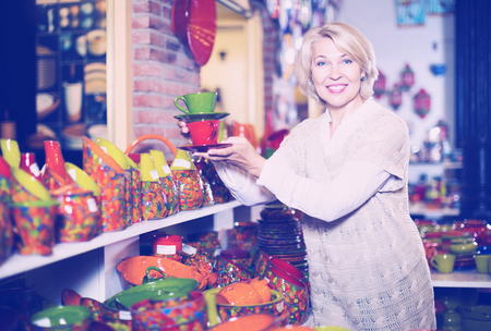 Portrait of smiling woman chooses ceramic ware in the cookware section at hypermarket Stock Photo