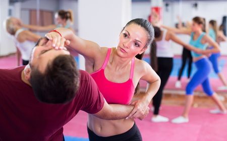 Sporty girl with her trainer are doing self-defence moves in gym