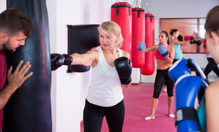 mature female is doing exercises with punching bag in sporty gym Stock Photo