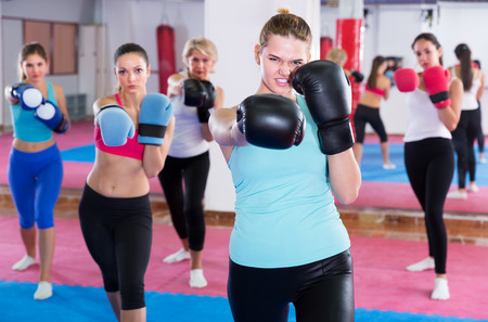 Portrait of concentrated girl who is boxing with group in sporty gym