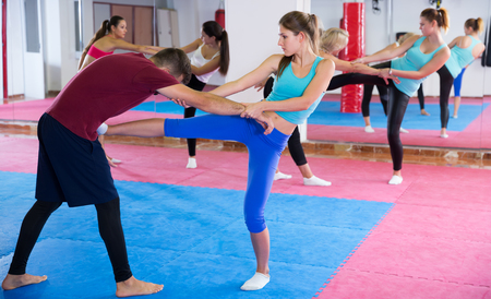 Nice females are doing self-defence-karate moves with trainer in sporty gym