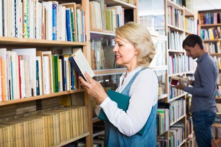 portrait of elderly  woman reading open book standing among bookshelves