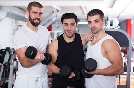 Portrait of three smiling sporty guys during workout in training room