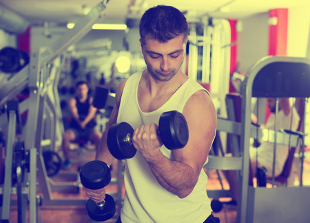 Muscular young man doing exercises with dumbbells at gym