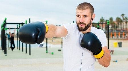 Athletic man in boxing gloves fulfills blows under the open sky Stock Photo