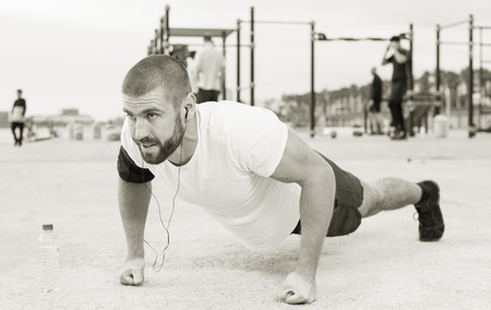 Strong man performs push-ups on an outdoor sports field