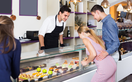 Smiling seller helping friends to choose sweets in comfortable cafe