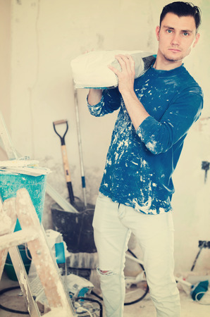 Young serious worker standing with bag of putty in hands in repairable room Stock Photo