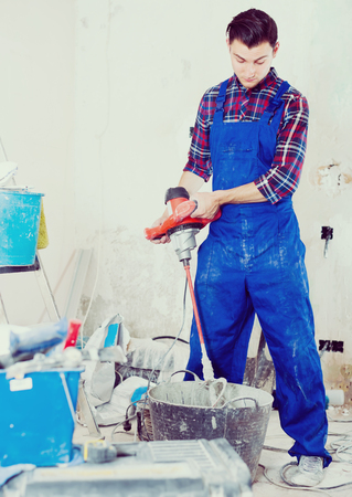 attentive builder mixing plaster in bucket using electric mixer in repairable room