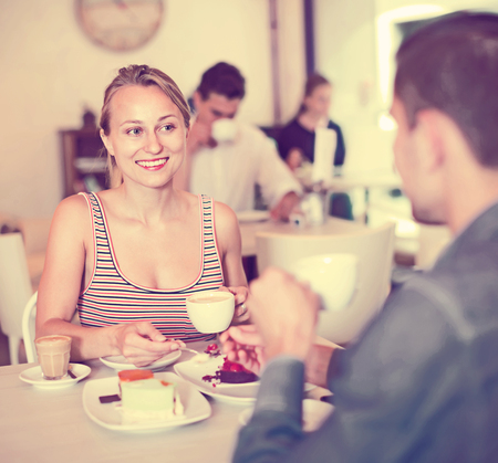 Ordinary smiling couple spending time together in cozy tearoom