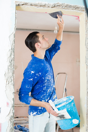 Construction worker wearing casual clothing with wall plastering tools renovating apartment house