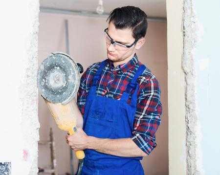 Construction worker cutting concrete wall by using handheld circular saw 版權商用圖片