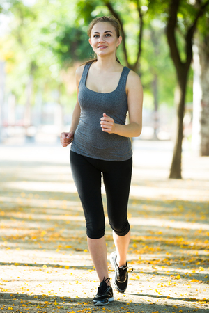 Young happy italian female in sportwear running in the sunny park  Stock Photo