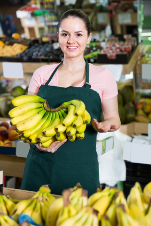 young attractive salesgirl proposing fresh bananas behind the counter in supermarket