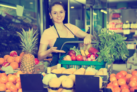 female grocery worker with range of vegetables and fruits in shopping basket Stok Fotoğraf