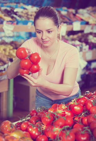Young woman looking for fresh tomatoes in vegetable store  Stock Photo